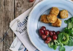 Käsekugeln mit Salat und Trauben auf einem Teller