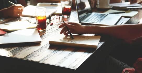 Holztisch mit Notebooks und Notizen