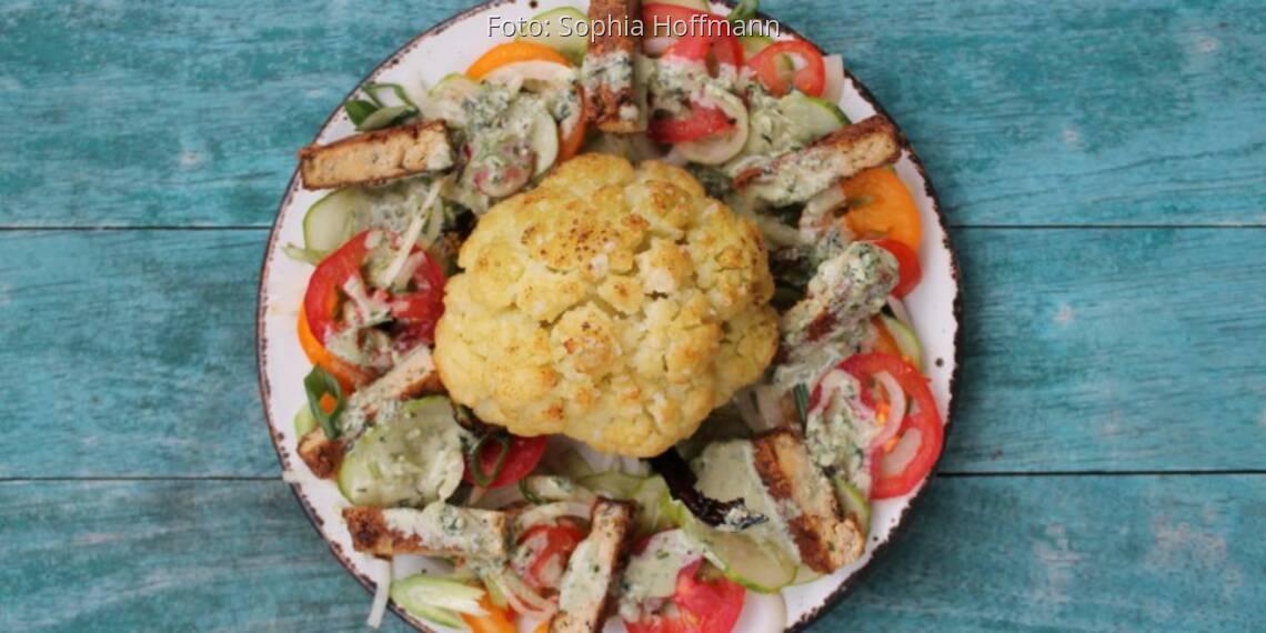 blaues Holzbrett und Teller mit ganzem gebackenen Blumenkohl und Gemüse