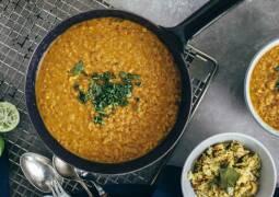 Indisches Dal in Schale angerichtete zusammen mit Tamarinden-Reis in Schale daneben