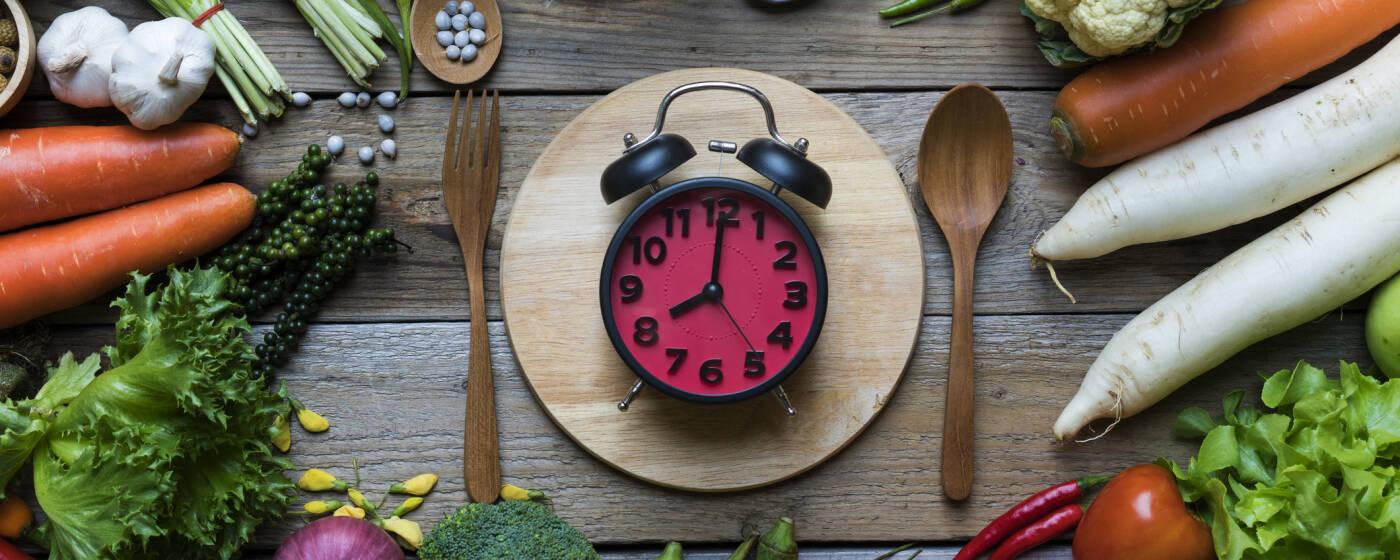 Wecker mit pinkem Ziffernblatt inmitten von Gemüse