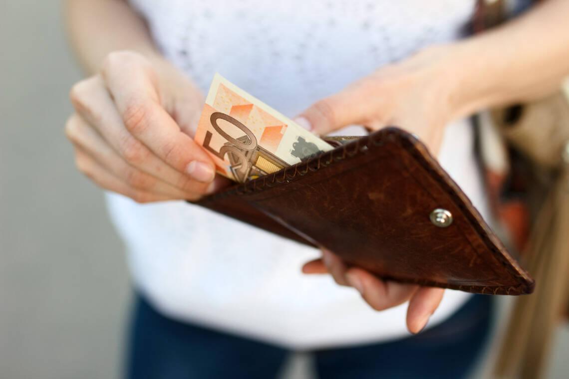 Frau zieht 50 Euro aus Geldbeutel