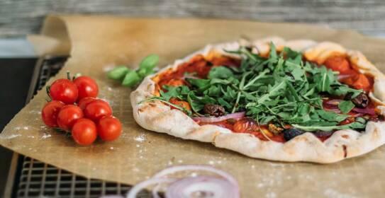 Vegane Pizza auf einem Blech, belegt mit Tomaten, Zwiebeln und Rucola.