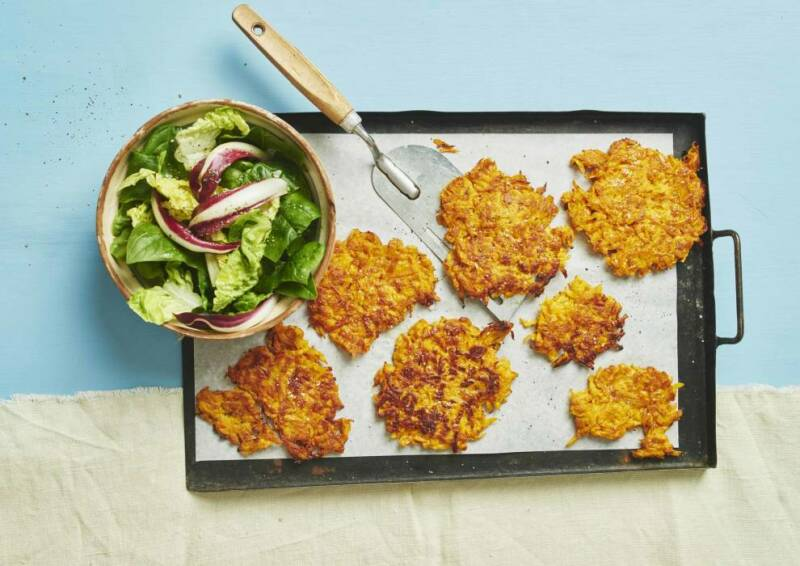 Leckere Puffer mit Salat dazu auf einem Blech vor blauem Hintergrund, von oben fotografiert.