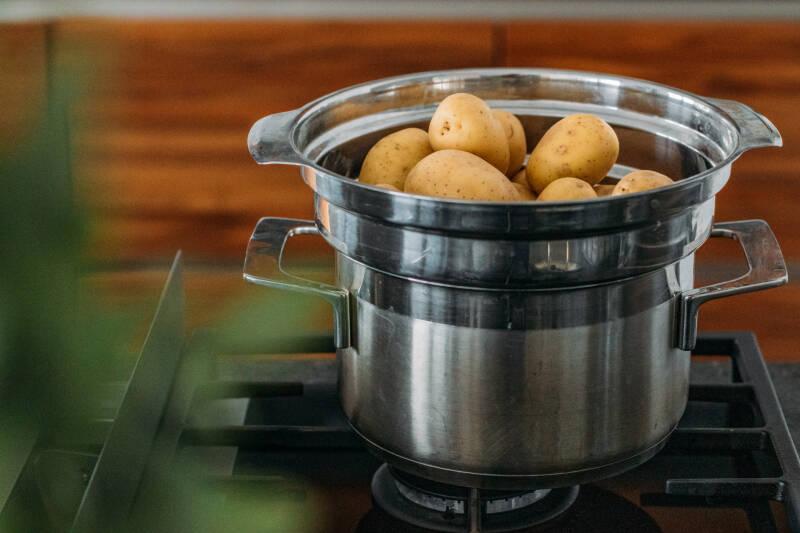 Kartoffeln Dämpfen  in Dampfgarer auf Gasherd vor dunklem Hintergrund.