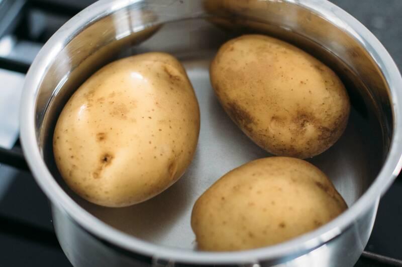 Kartoffeln in einem Topf mit kaltem Wasser, von oben fotografiert.