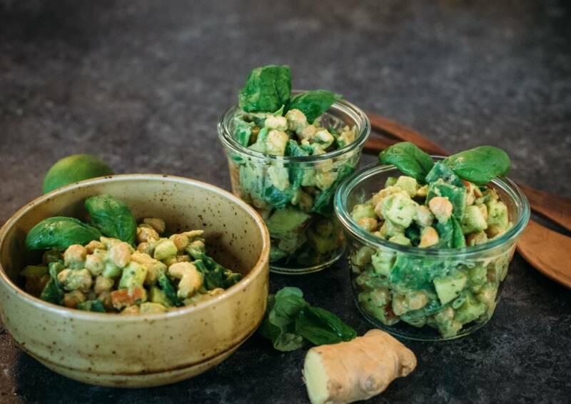 Kichererbsensalat mit Avocado-Dressing in kleinen Schälchen angerichtet, garniert mit Basilikum