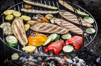 Zucchini, Paprika und anderes Gemüse auf einem frei schwebenden Dreibeingrill