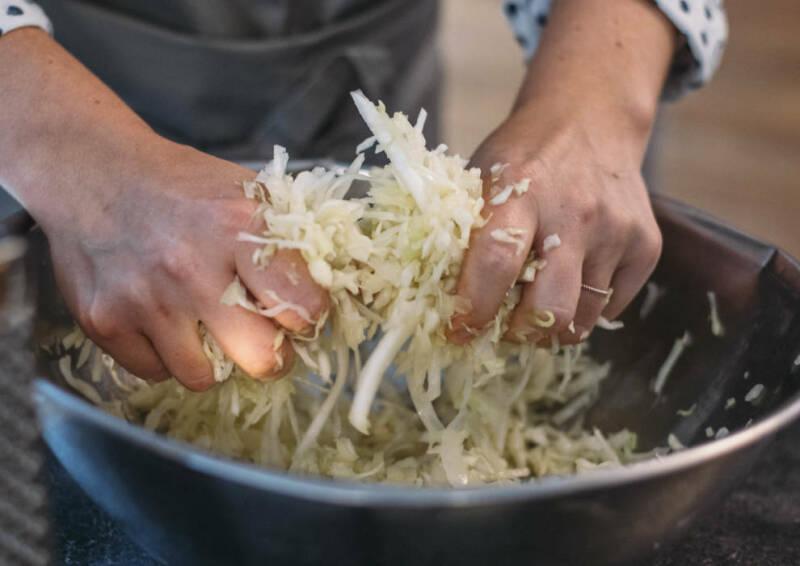 Kohlstreifen werden in einer Metallschüssel mit den Händen geknetet.