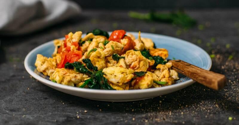 Blauer Teller gefüllt mit Rührei, Tomaten und Spinat, vor dunkelgrauem Hintergrund. Von der Seite fotografiert.