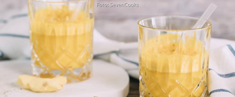 Gelber Kurkuma-Ingwer Immunbooster in zwei Gläsern mit Strohhalm.