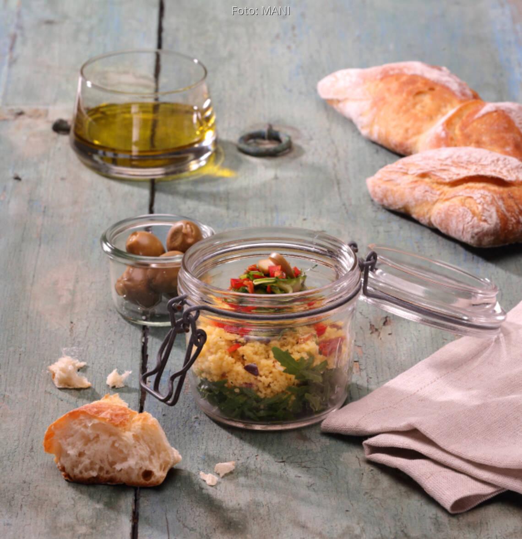 Glas mit Maistaboulet mit Olivenöl, Fladenbrot auf Holztisch
