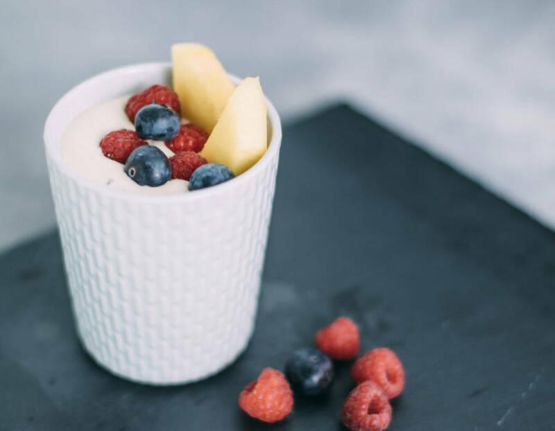 Mango-Quark-Dessert mit Früchten in Becher vor dunklem Hintergrund.