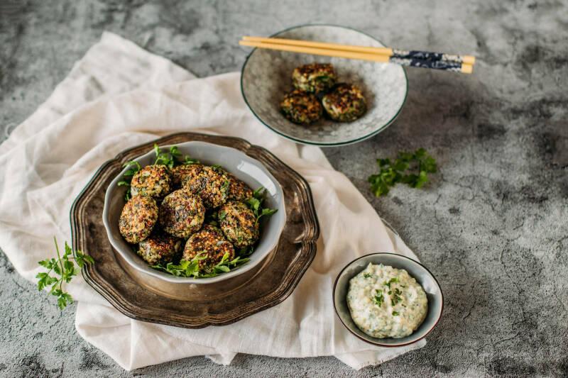 Mangold Quinoa Bratlinge auf Tellern mit Stäbchen und Soße vor dunklem Hintergrund.
