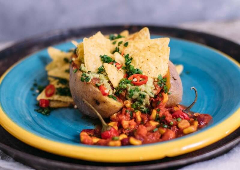 Ofenkartoffel auf mexikanische Art: gefüllt mit Mais, Käse und Tacos. Von vorne fotografiert.