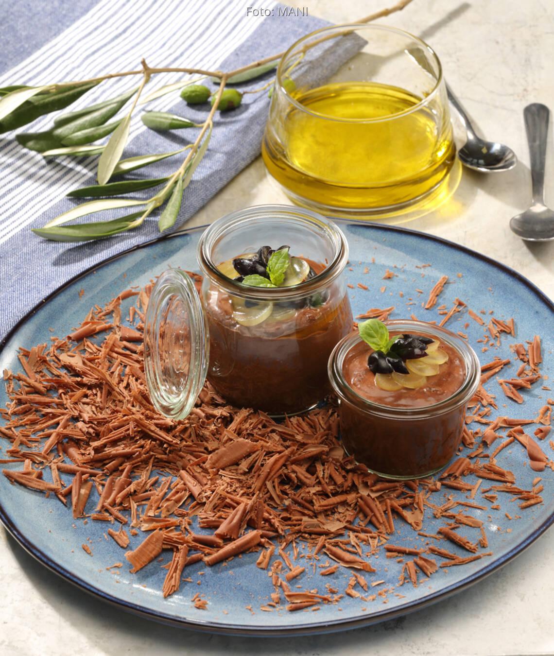 Schokomousse in Gläschen auf blauem Teller mit Olivenöl und Tuch dekoriert