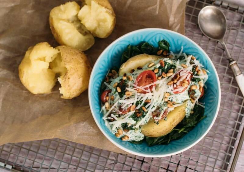 Ofenkartoffel gefüllt mit Spinat-Ricotta-Sauce, dazu Pinienkerne und Tomaten. Von oben fotografiert auf einem Gitter, daneben ein Löffel.