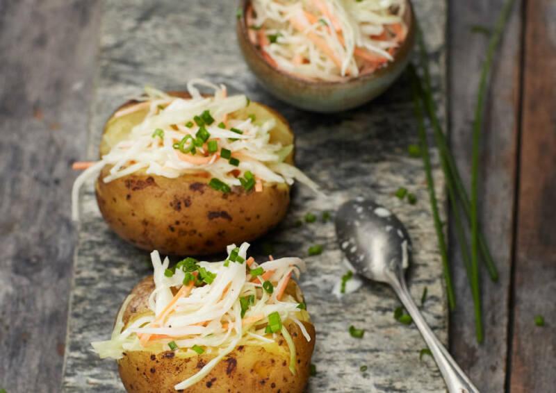 Ofenkartoffeln auf einem Teller, mit frischem Cole Slaw gefüllt. Von oben fotografiert.