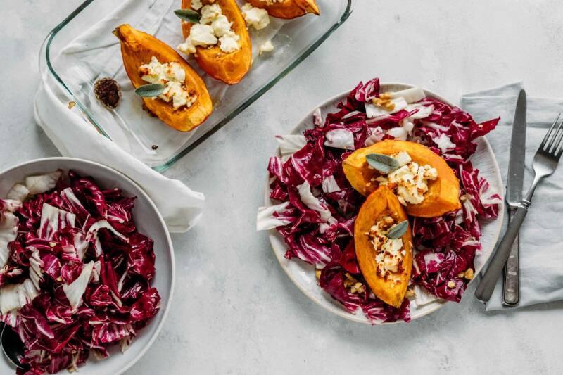 Ofenkürbis mit nussigem Herbstsalat und Radicchio auf Tellern und Schüsseln vor weißem Hintergrund.