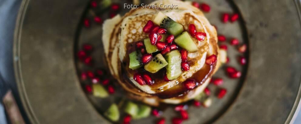 Stapel Pancakes von oben mit Kiwi und Granatapfel