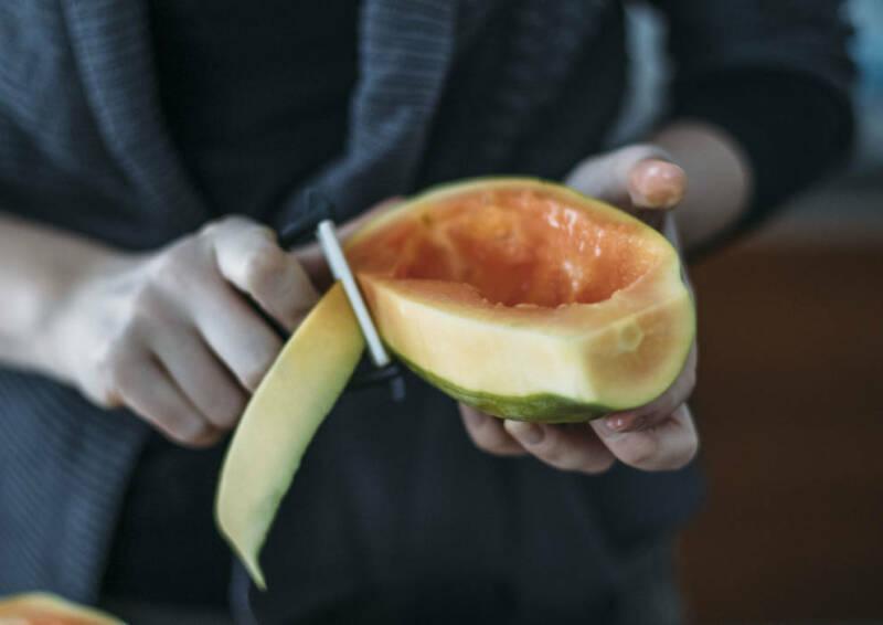 Eine halbe Papaya wird mit Sparschäler geschält.