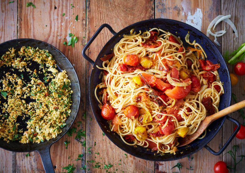 Leckere Spaghetti mit Ofentomaten in einer Pfanne, von oben fotografiert.