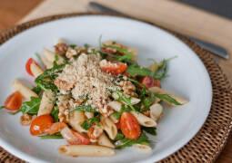 Teller mit Penne, Pucola, frischen Tomaten und veganem Parmesan