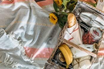Gefüllter Picknickkorb mit Baguette, Sandwich, Obst und Getränken
