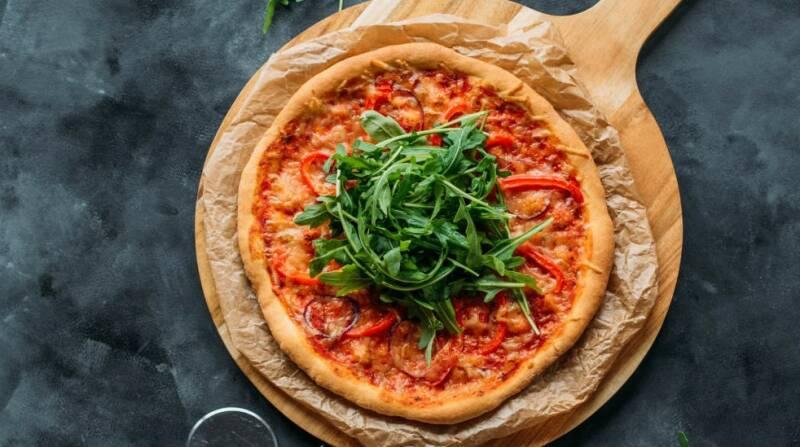 Pizza mit veganem Käse, Tomaten und Rucola von oben fotografiert.