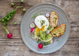 Baguettescheiben mit pochiertem Ei und Erbsenpüree auf grauem Teller