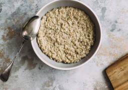 Porridge von oben mit Löffel und Holzbrett