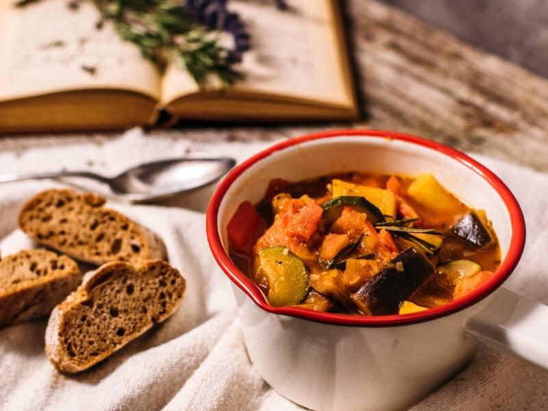 Der französische Klassiker mit leckerem Gemüse in einem kleinen Topf, dazu gibt es dunkles Baguette. Von oben fotografiert.
