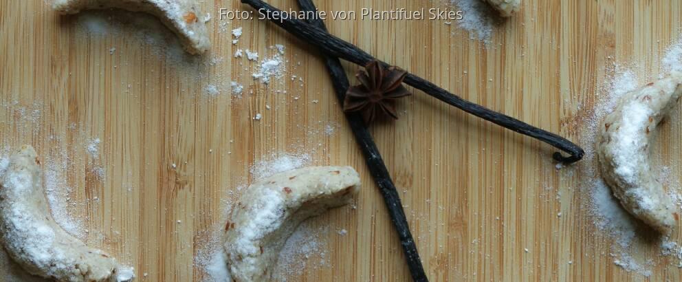 Rohe Vnaillekipferl auf Holzbrett mit Vanilleschote und Sternanis