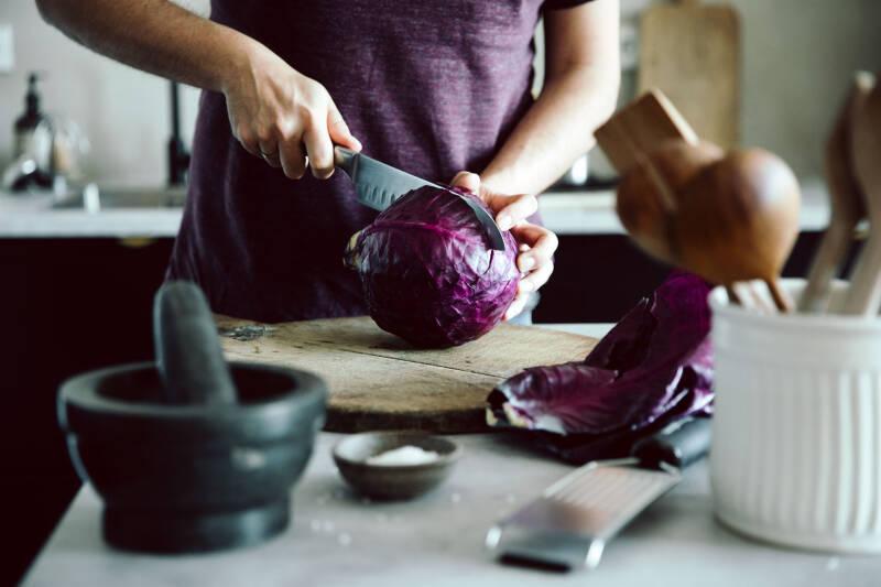Ein Rotkohl wird mit einem großen Messer auf einem Holzbrett durchgeschnitten.