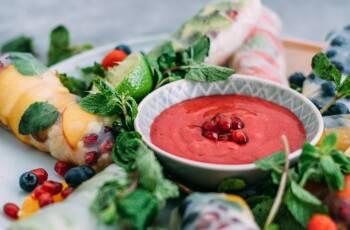Teller mit gefüllten Reispapierrollen. Darin befindet sich Obst der Saison: Heidelbeeren, Pfirsich, Himbeeren. In der Mitte steht ein knallig roter Dip auspürierten Himbeeren und Minze.