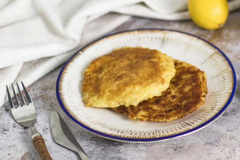 Selbst gemachte Kartoffelpuffer mit Sauerkraut auf einem weißen Teller.