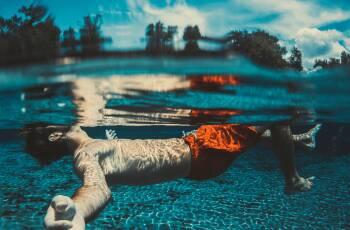 Junger Mann taucht im blauen Wasser