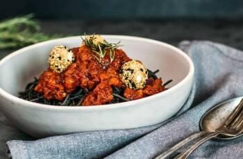 Schüssel gefüllt mir schwarze Bohnen Spaghetti, dazu Paprika Pesto und in Sesam panierte Mozzarellabällchen. Von oben/seitlich fotografiert.