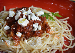 Roter Teller mit Spaghetti, sonnengetrockneten Tomaten und zerbröseltem Feta