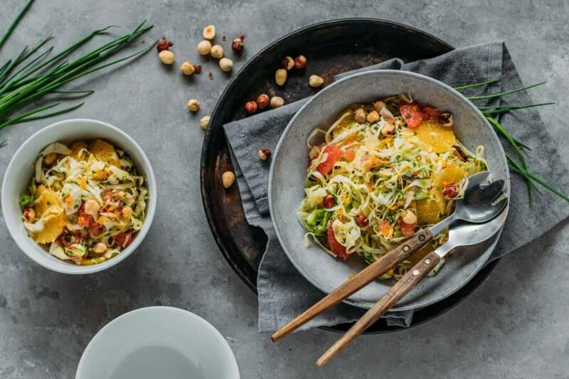 Spitzkohlsalat in Teller und Schüssel neben Schnittlauch vor hellem Hintergrund.