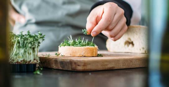 Frische Kresse wird auf ein Brot mit Butter gelegt