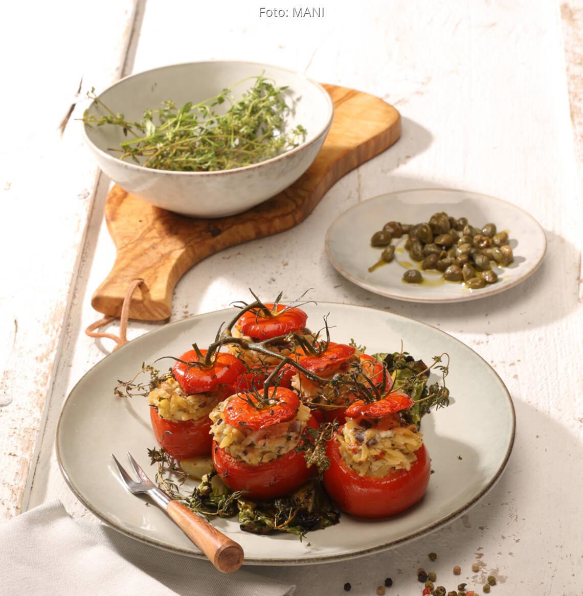 Gefüllte Tomaten auf weißem Teller mit Salat und Kapern auf kleinem Teller