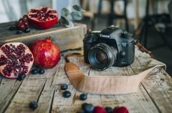 Kamera und Granatapfel halbiert auf einem Holzbrett