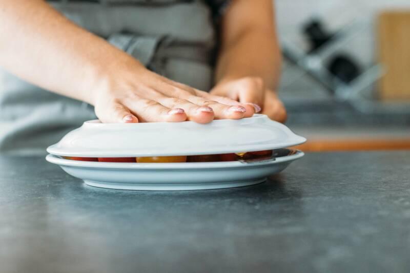 Schritt 3: Während man den oberen Teller fixiert, schneidet man mit der anderen Hand zwischen den Tellern durch, um Tomatenhälften zu erhalten.
