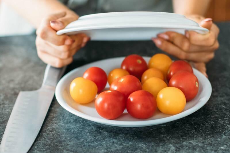 Schritt 2: Man platziert den zweiten Teller über den Tomaten im ersten Teller.
