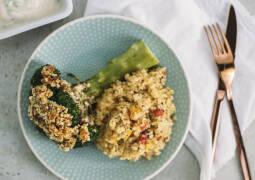 Teller mit überbackenem Brokkoli mit Paranusskruste, Bulgur-Gemüse und Besteck daneben