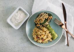 Heller Tisch mit hellblauem Teller mit überbackenem Brokkoli und Bulgur-Gemüse