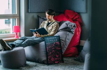 """Junger Mann sitzt in Sitzsack und schreibt in Notizbuch (daneben eine Tafel """"Zuckerfalle"""""""