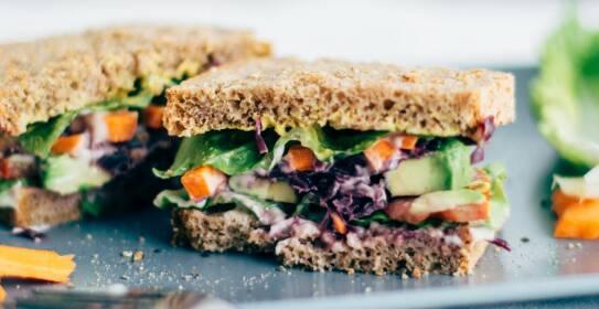 Alles, was du über vegane Ernährung wissen musst, erfährst du in diesem Artikel. Außerdem gibt es viele leckere Rezepttipps, wie dieses Avocado-Veggie Sandwich. Sandwich auf einer Platte mit Salat und Karotten.