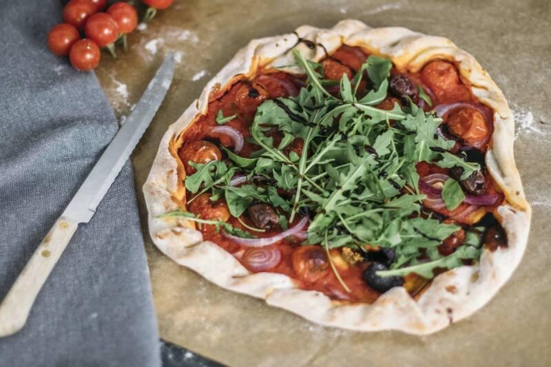 Vegane Pizza aus Bierteil auf Backpapier, daneben frische Tomaten